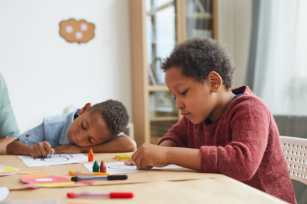 Retrato de um menino afro-americano desenhando com giz de cera enquanto aproveita a aula de arte na pré-escola
