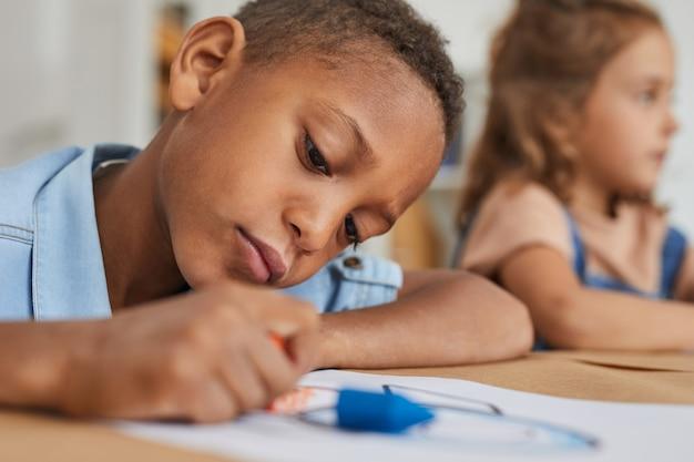 Retrato de um menino afro-americano desenhando com giz de cera enquanto desfruta de uma aula de arte na pré-escola ou no centro de desenvolvimento