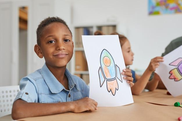 Retrato de um menino afro-americano fofo mostrando fotos de um foguete espacial e sorrindo enquanto desfruta da aula de arte na pré-escola ou centro de desenvolvimento infantil