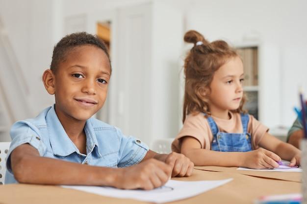 Retrato de um menino afro-americano sorrindo enquanto desenha com giz de cera durante a aula de arte na pré-escola
