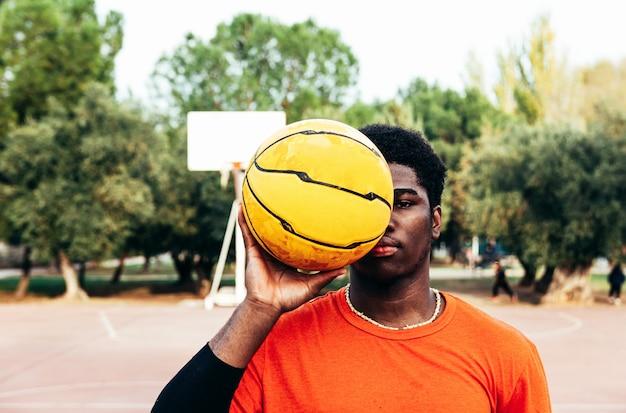 Retrato de um menino afro-negro cobrindo o olho com uma bola de basquete. cesta de basquete em segundo plano.
