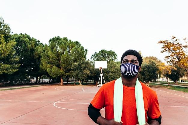 Retrato de um menino afro-negro com uma máscara facial e uma toalha verde em uma quadra de basquete de rua. esporte em tempos de pandemia.