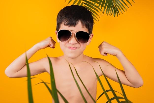 Retrato de um menino alegre de óculos escuros, mostrando seus bíceps em um fundo amarelo.