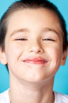 Retrato de um menino alegre e sorridente com dermatite perioral leve em um fundo azul