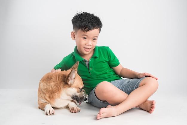 Retrato de um menino alegre se divertindo com o cachorro corgi galês no chão