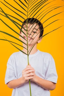 Retrato de um menino alegre, segurando uma folha de palmeira em um fundo amarelo.