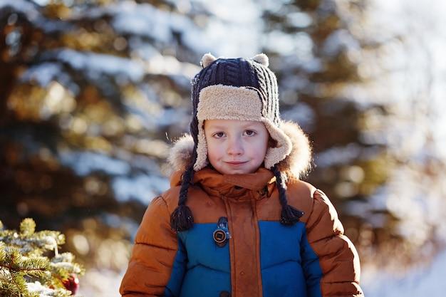 Retrato de um menino andando na natureza de inverno. brincando com neve. infância feliz do conceito