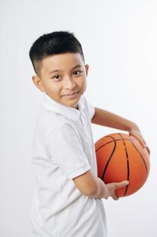 Retrato de um menino asiático pré-adolescente sorridente e fofo posando com uma bola de basquete