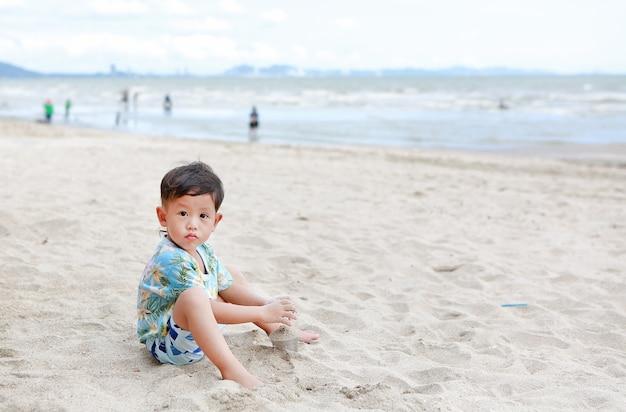 Retrato de um menino asiático se divertindo com a areia na praia
