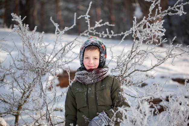 Retrato de um menino bonitinho em roupas quentes, brincar ao ar livre durante a queda de neve em dia ensolarado de inverno.