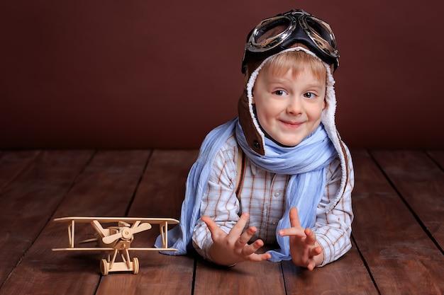 Retrato de um menino bonito com capacete de piloto e lenço azul com um avião de madeira