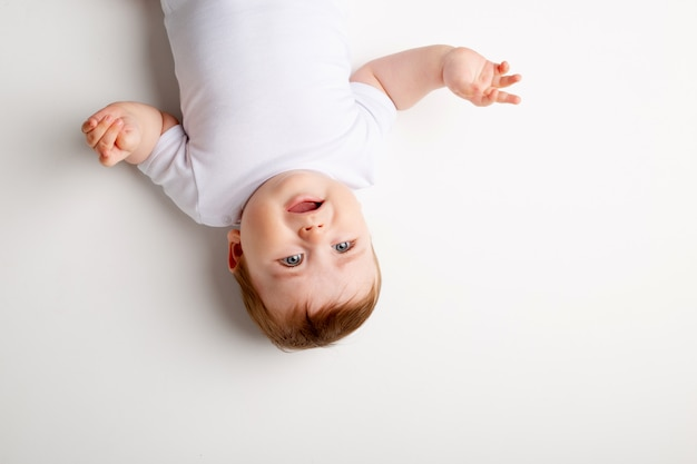 Retrato de um menino bonito com olhos azuis em uma roupa branca