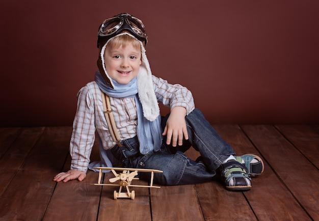 Retrato de um menino bonito em um capacete de piloto com um avião de madeira