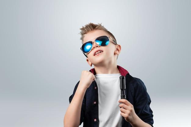 Retrato de um menino bonito em um fundo cinza. o menino de óculos escuros.