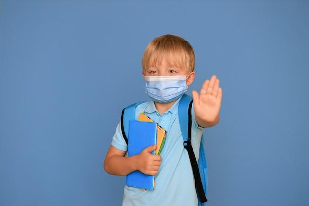 Retrato de um menino bonito estudante 6 anos de idade com uma mochila brilhante sobre um fundo azul. de volta à escola.