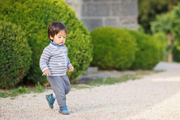 Retrato de um menino bonito oriental brincando ao ar livre no parque
