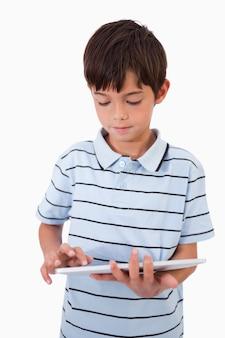 Retrato de um menino bonito usando um tablet computador