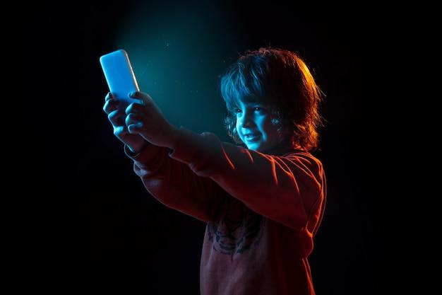 Retrato de um menino branco isolado no fundo escuro do estúdio sob luz de néon