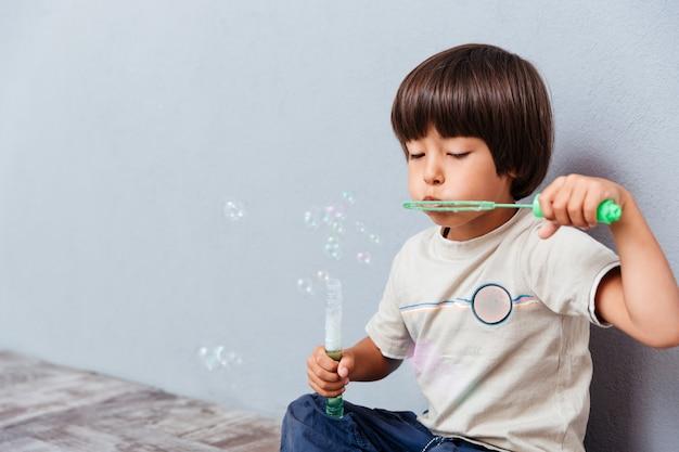 Retrato de um menino brincando e soprando bolhas de sabão