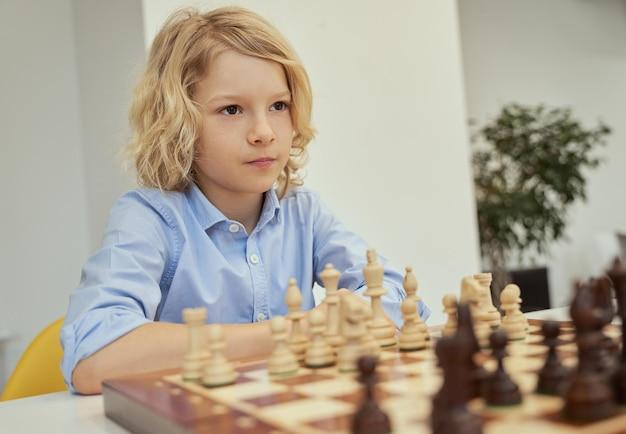 Retrato de um menino caucasiano calmo de camisa azul, sentado na sala de aula e desviando o olhar enquanto