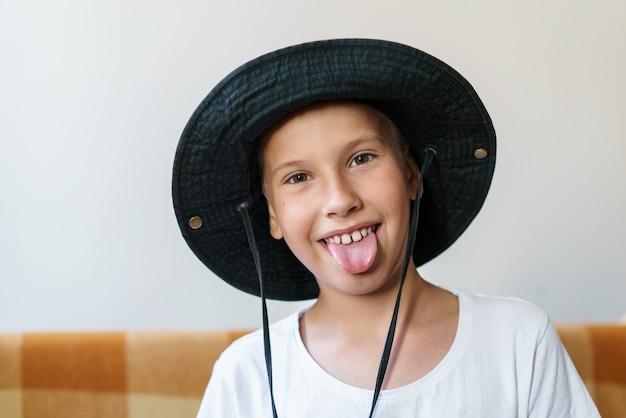 Retrato de um menino caucasiano encantador com camiseta branca e chapéu-panamá preto sob o sol da manhã em l