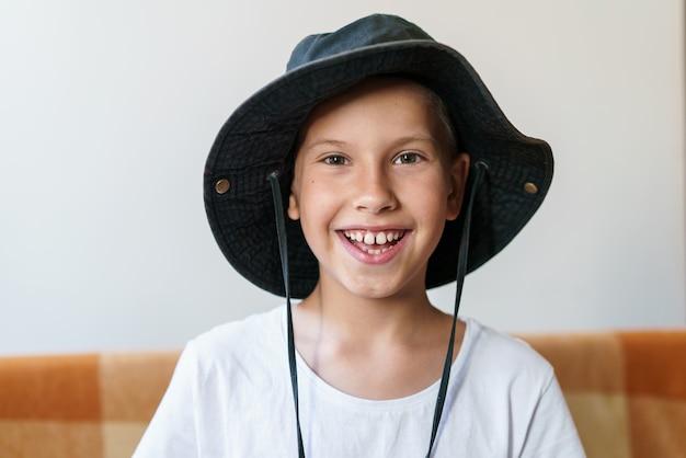 Retrato de um menino caucasiano encantador em camiseta branca e chapéu-panamá preto na luz do sol da manhã no ...