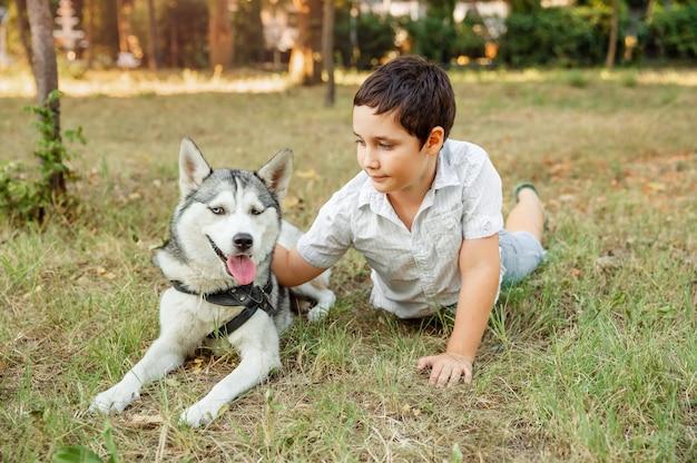 Retrato de um menino caucasiano feliz com seu cachorrinho deitado no gramado