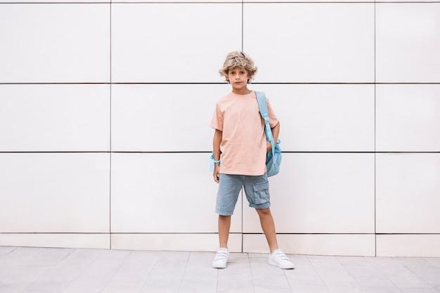 Retrato de um menino caucasiano feliz com uma mochila, esperando que seus colegas de classe entrem na escola. primeiro dia de aula.