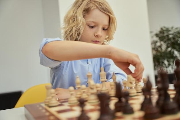 Retrato de um menino caucasiano inteligente com camisa azul, sentado na sala de aula e se mexendo enquanto