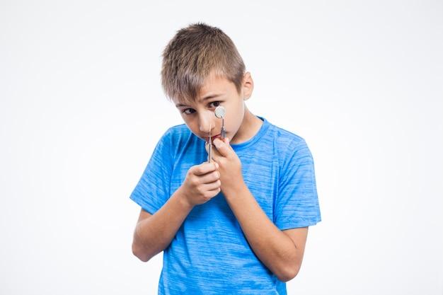 Retrato, de, um, menino, com, espelho dental, e, scaler, contra, fundo branco