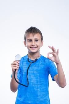 Retrato, de, um, menino, com, estetoscópio, gesticule, tá bom sinal