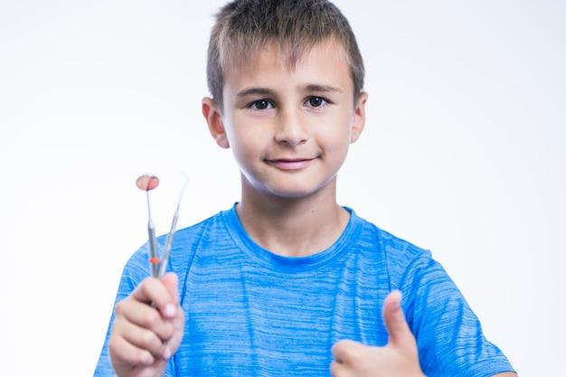 Retrato, de, um, menino, com, instrumentos dental, gesticule, polegares cima