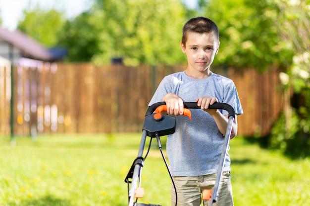 Retrato de um menino com um cortador de grama elétrico cortando a grama.