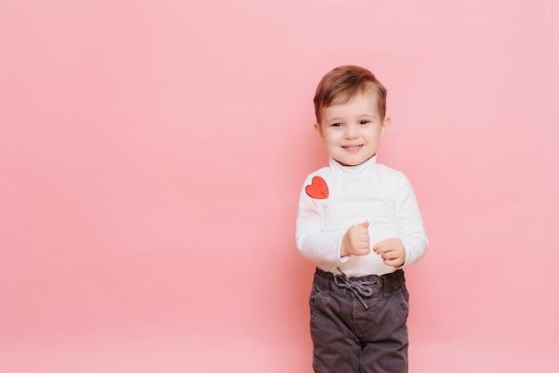 Retrato de um menino com um pirulito em forma de coração na mão.