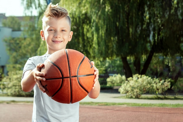 Retrato de um menino com uma bola de basquete em uma quadra de basquete