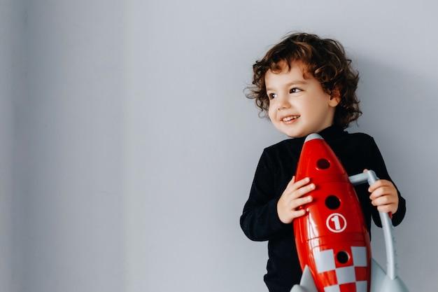 Retrato de um menino com uma nave espacial vermelha nas mãos em uma parede cinza