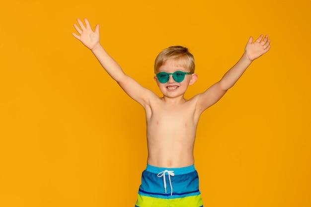 Retrato de um menino criança feliz 6-7 anos de idade em shorts de natação em um espaço amarelo, mar e verão
