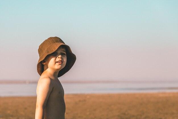 Retrato de um menino de 3 anos de idade com um chapéu-panamá marrom na praia. copie o espaço