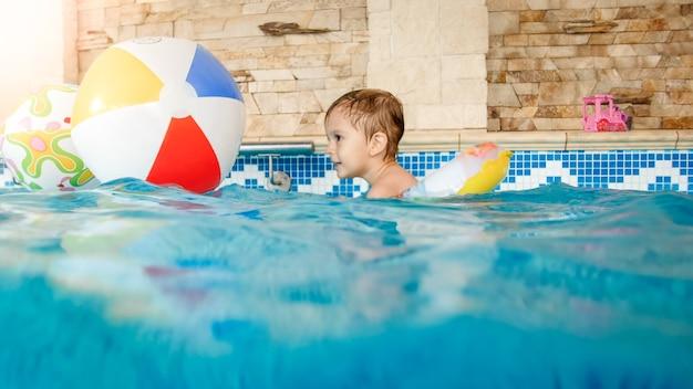 Retrato de um menino de 3 anos rindo e sorrindo, nadando com um anel inflável colorido e brincando com uma bola de praia na piscina