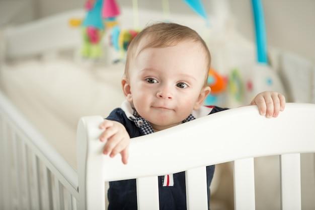 Retrato de um menino de 9 meses em um berço branco