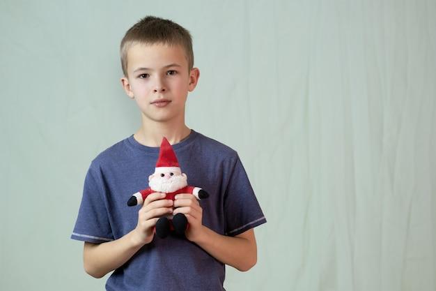 Retrato de um menino de criança brincando com um pequeno brinquedo de papai noel.