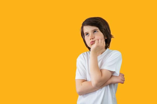 Retrato de um menino de nove anos vestindo uma camiseta branca, pressionando a mão no rosto, pensando seriamente e olhando para cima