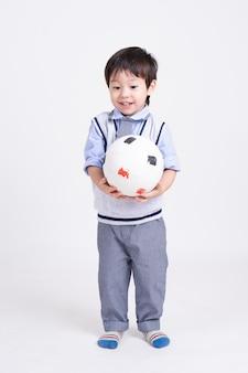 Retrato de um menino de pé com sorrindo, segurando uma bola de futebol na mão