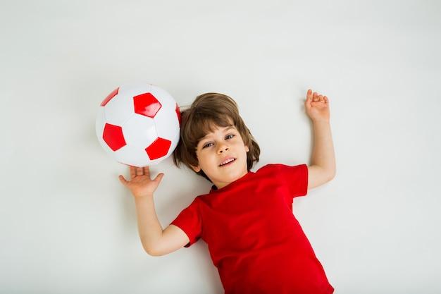 Retrato de um menino deitado com uma bola de futebol em uma superfície branca com espaço para texto