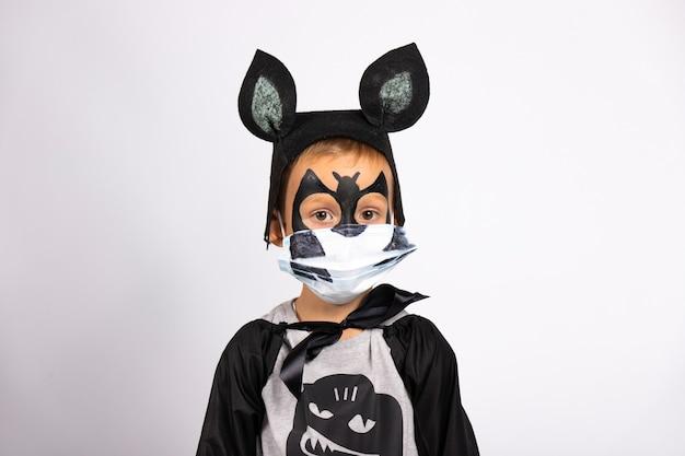 Retrato de um menino disfarçado de morcego. ele está usando uma máscara médica protetora com um sorriso engraçado pintado nela.