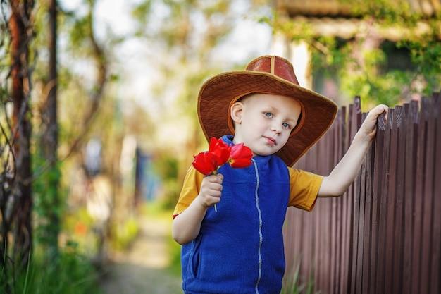 Retrato de um menino em pé com um grande chapéu com um buquê de tulipas na cerca de madeira na zona rural