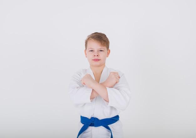 Retrato de um menino em um quimono branco com um gesto proibitivo em uma parede branca