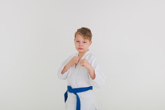 Retrato de um menino em um quimono branco com uma faixa azul em uma pose em um fundo branco