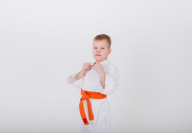 Retrato de um menino em um quimono branco com uma faixa laranja em uma pose em uma parede branca