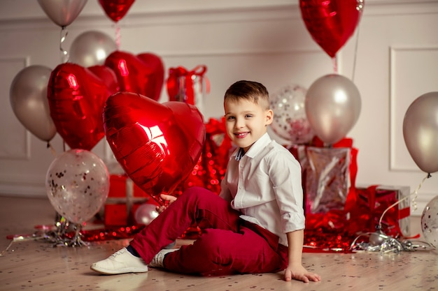 Retrato de um menino em uma camisa branca e calça vermelha no fundo da decoração festiva de bolas vermelhas no widget de corações e presentes. aniversário de férias ou dia dos namorados